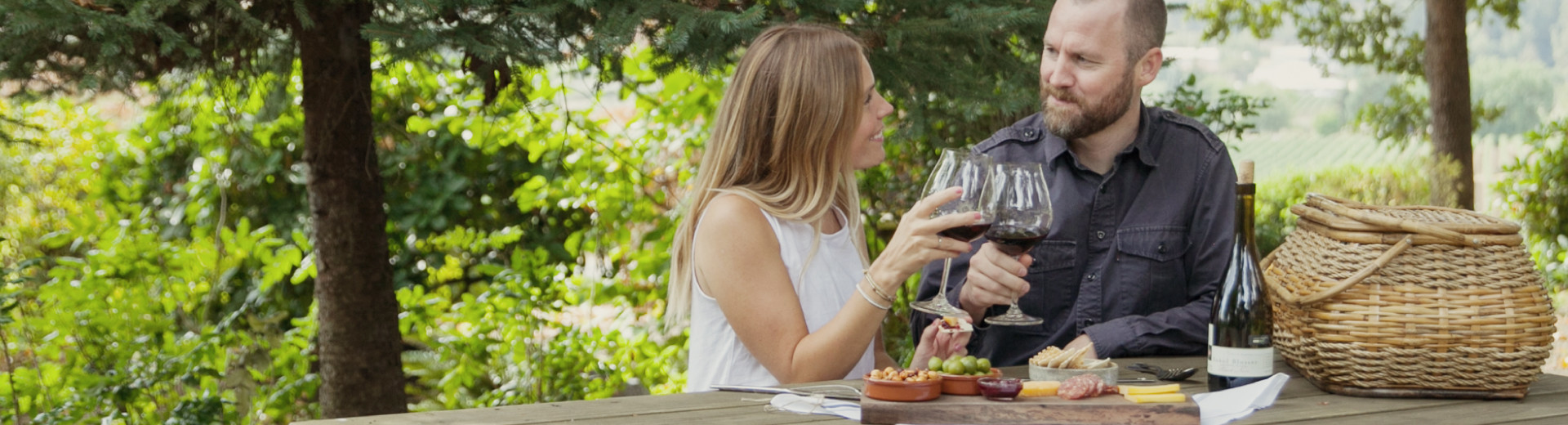 Atticus Hotel guests toast during a vineyard picnic